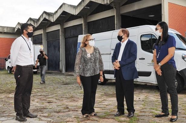 Imagem colorida. Dois homens e duas mulheres em pé em terraço que antecede garagem de carros, entre eles o presidente Lourival Serejo. Ao fundo um veículo tipo van de cor branca. Em segundo plano, um homem está com celular ao ouvido.