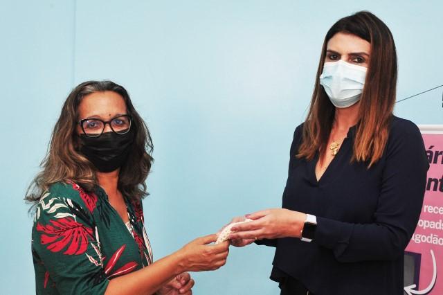 Imagem colorida. Foto do lançamento da Campanha Sou Solidário - Sou Sustentável. A artesã voluntária Regina Lima entrega um kid ecopad à juíza Lorena Brandão.