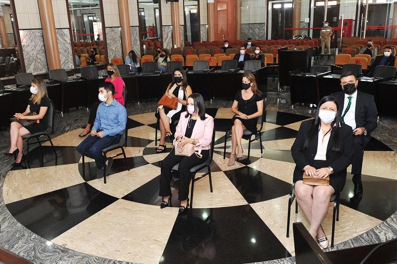 Fotografia colorida. Imagem da Sala das sessões Plenárias do TJMA, com oito pessoas sentadas em cadeiras ao centro e poltronas da plateia ao fundo
