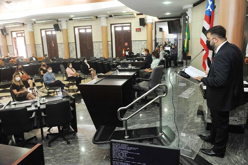 Fotografia colorida. Imagem da Sala das sessões Plenárias do TJMA, com autoridades à mesa principal e oito pessoas sentadas em cadeiras ao centro.