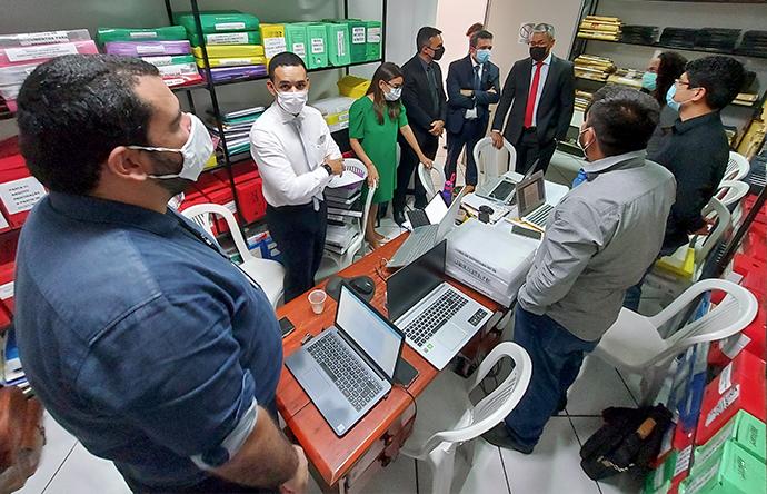 Pessoas de pé conversam em sala de arquivo de processos