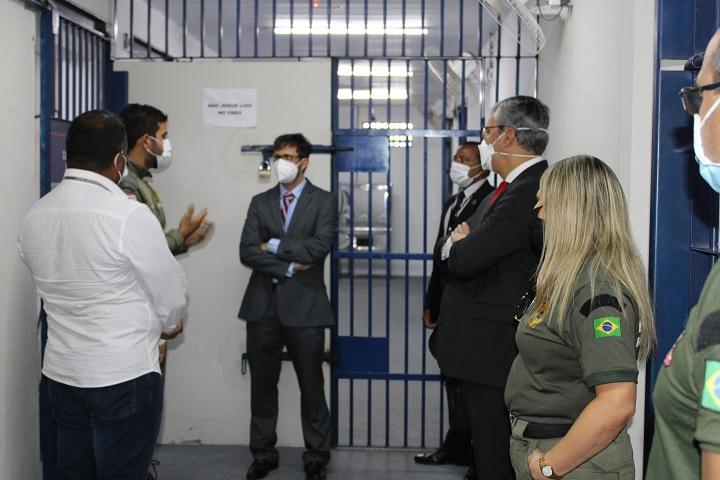 Imagens contendo várias pessoas, denotando uma visita a uma penitenciária