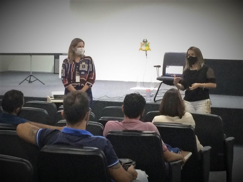 Coordenadora de planejamento da CGJ-MA, e juíza diretora do Fórum, de pé, falam para servidores em auditório, sentados