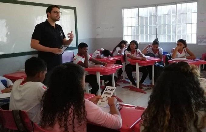 Homem branco, alto, de camiseta preta, fala em sala de aula para estudantes