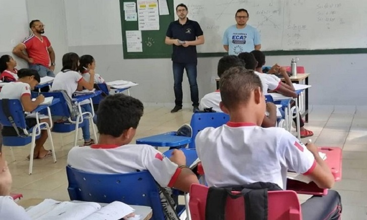 Dois homens brancos, um alto, de camiseta preta, e outro baixo, de camiseta azul clara, falam para uma sala de aula com estudantes sentados em carteiras