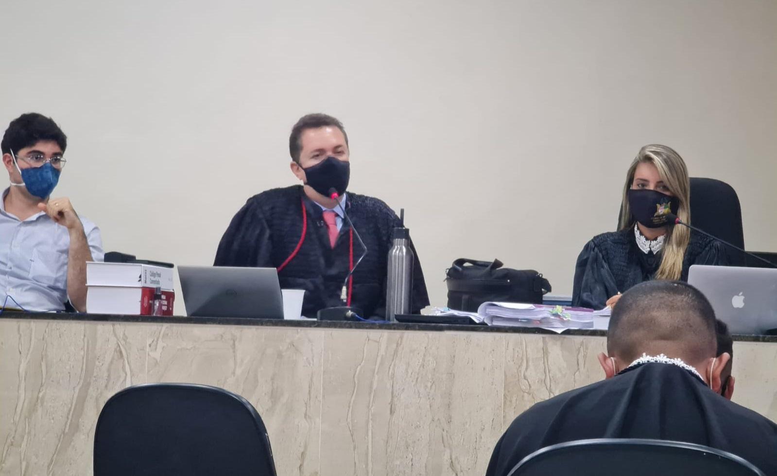 Dois homens brancos, um de roupa branca e outro de toga preta, e mulher loura, de toga preta, sentados em mesa do Tribunal do Júri.